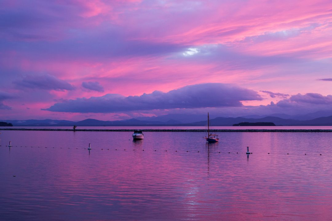Purple sunset with boats in the water with clouds