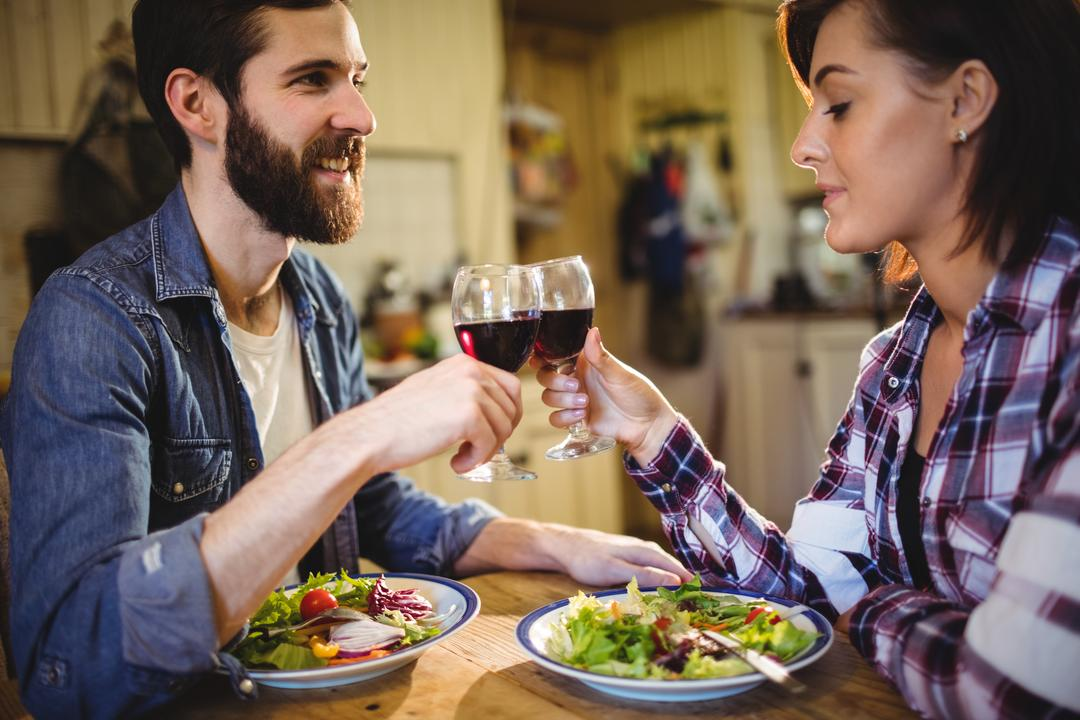 Couple toasting glasses of wine at home