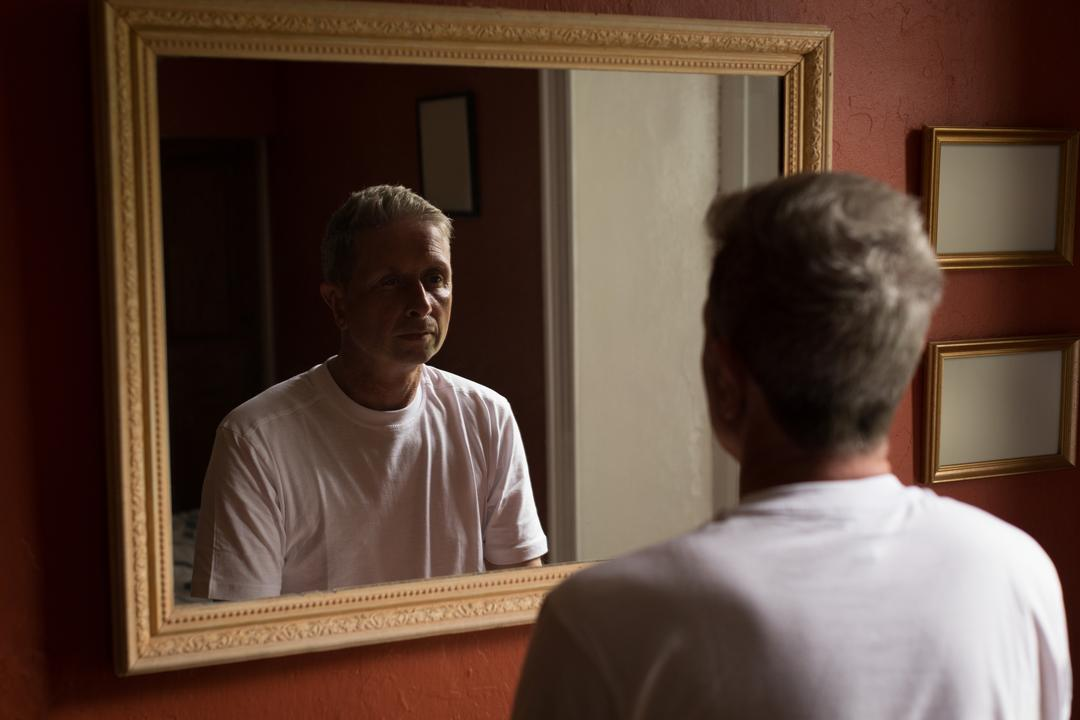 Senior man looking at mirror in bathroom at home