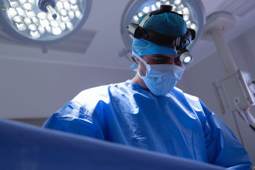 Low angle view of male surgeon with headlight performing surgery in operation room at hospital