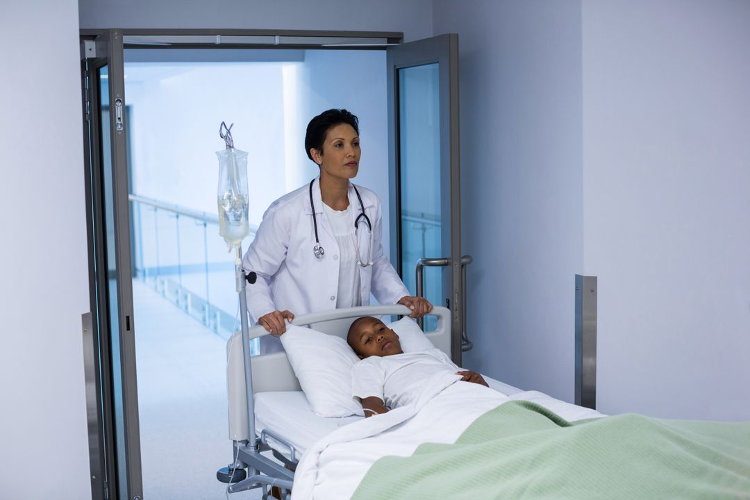 Doctor pushing emergency stretcher bed in corridor at hospital Free Stock Images from PikWizard
