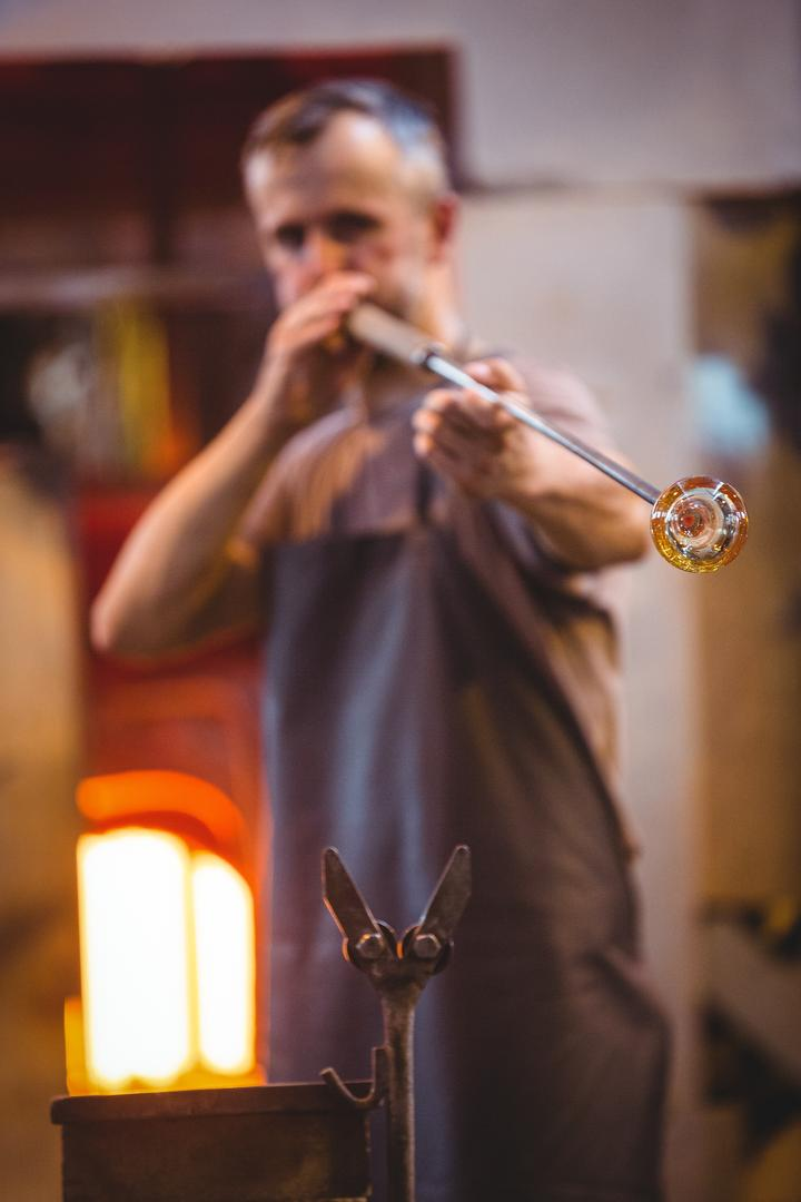 Glassblower shaping a glass on the blowpipe at glassblowing factory