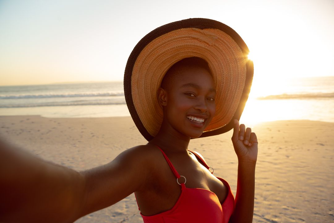 Portrait of happy woman in hat standing on the beach