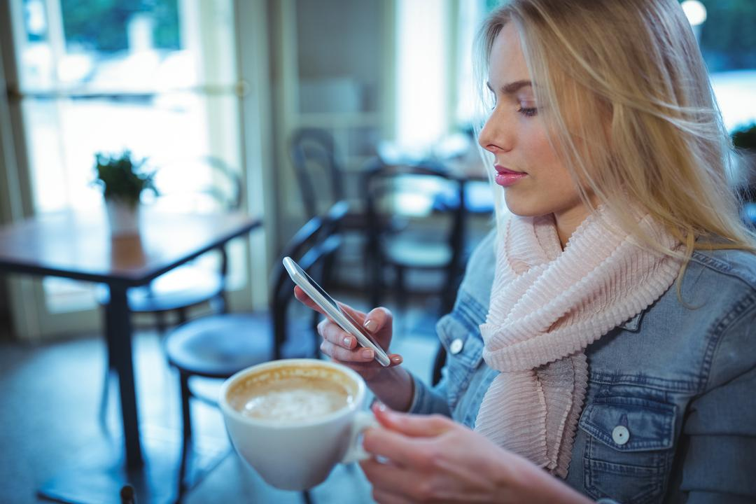 Woman using mobile phone while having coffee in café