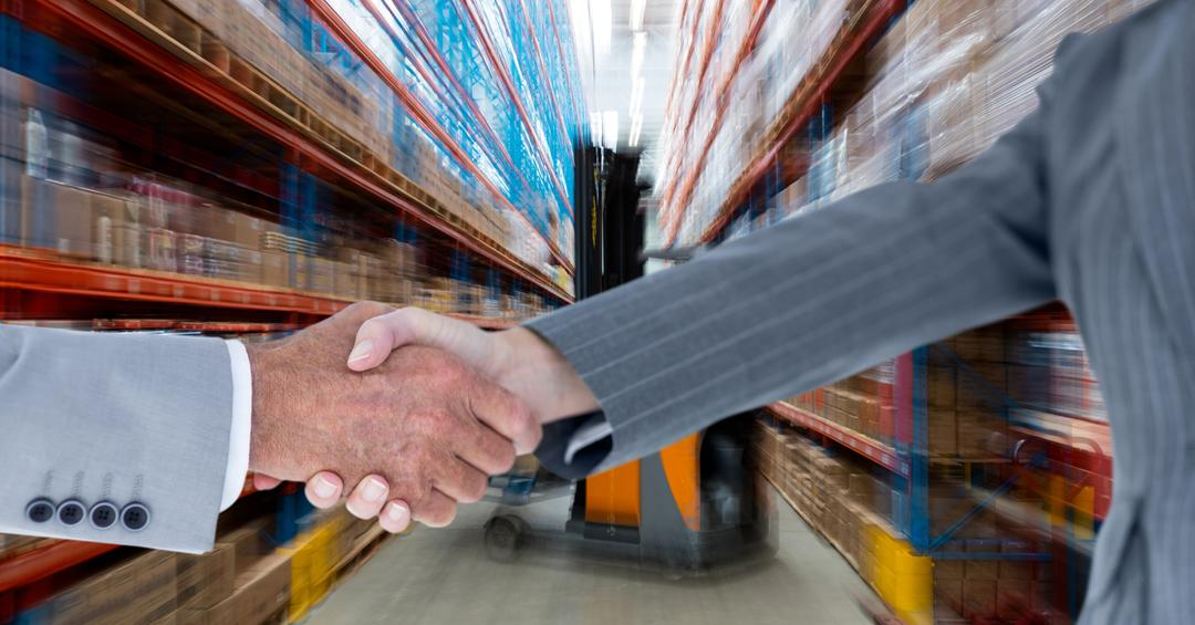 Digital composite of Cropped image of business people doing handshake in warehouse Free Stock Images from PikWizard