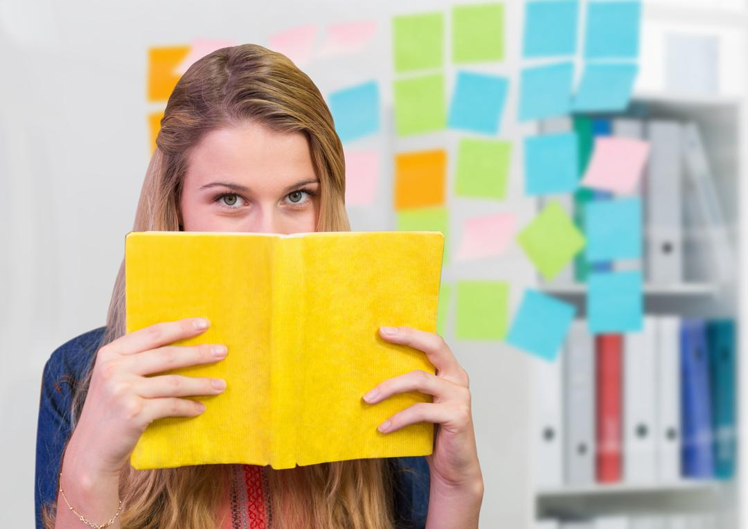 Portrait of woman holding a book against sticky notes in background