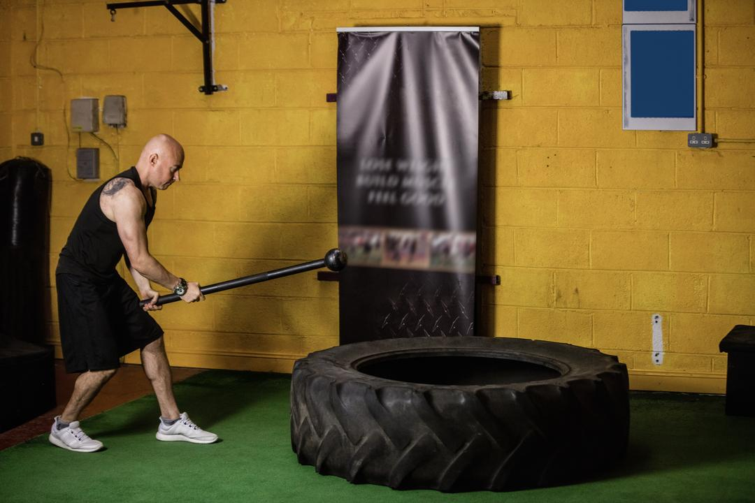 Thai boxer hitting tyre with sledge hammer in the fitness studio