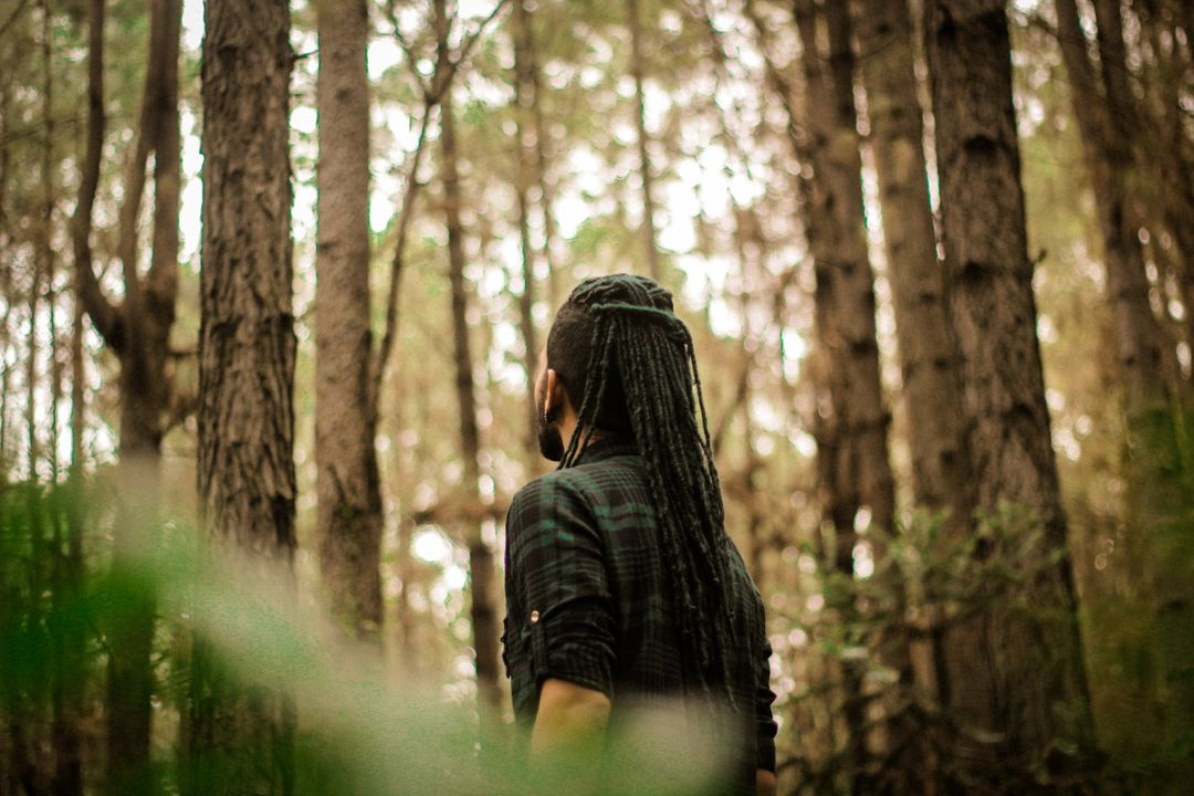 Man looking into the distance in a forest