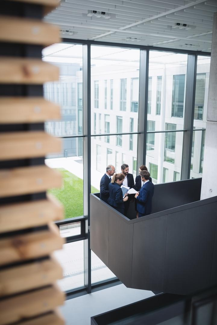 Group of businesspeople having a discussion near staircase in office Free Stock Images from PikWizard