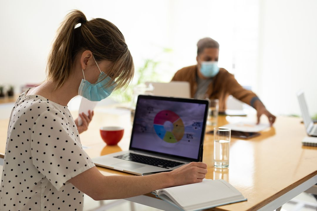 Caucasian woman wearing a facemask looking at her notes while holding a piece of paper with her other hand. On the table are laptops with graphs, a cup of coffee, and glasses of water. Free Stock Images from PikWizard