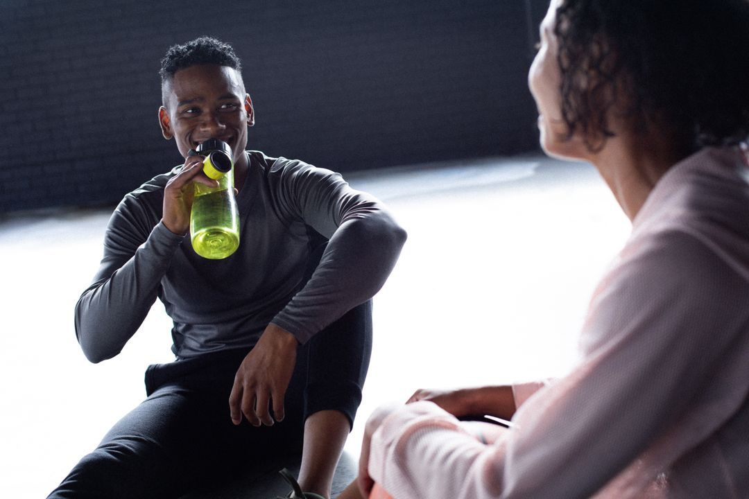 African american man and woman sitting resting drinking water and talking in empty building. Urban fitness healthy lifetyle. Free Stock Images from PikWizard