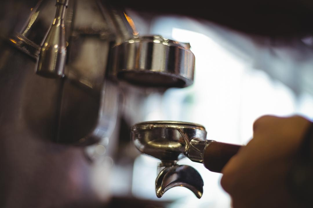 Waitress holding portafilter filled with ground coffee in cafe