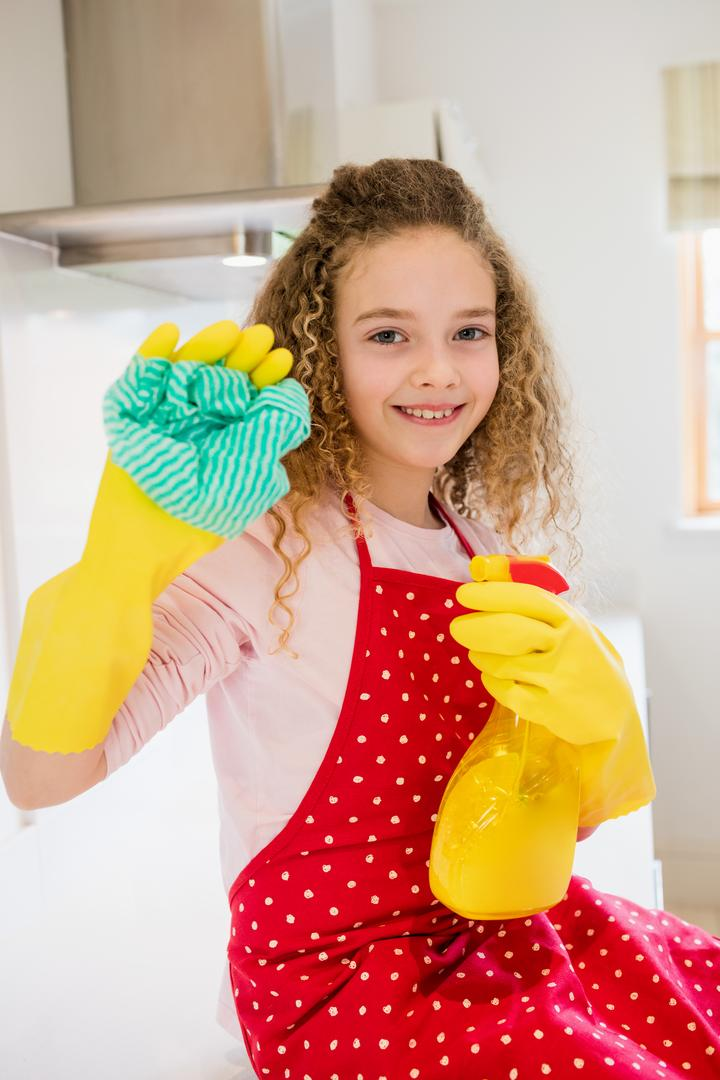 Portrait of happy girl holding napkin and spray bottle in kitchen at home
