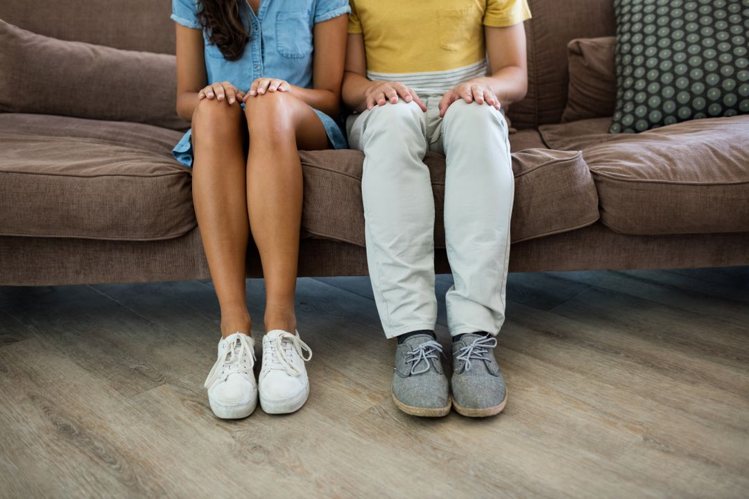 Couple sitting with hands on thighs in the living room at home Free Stock Images from PikWizard