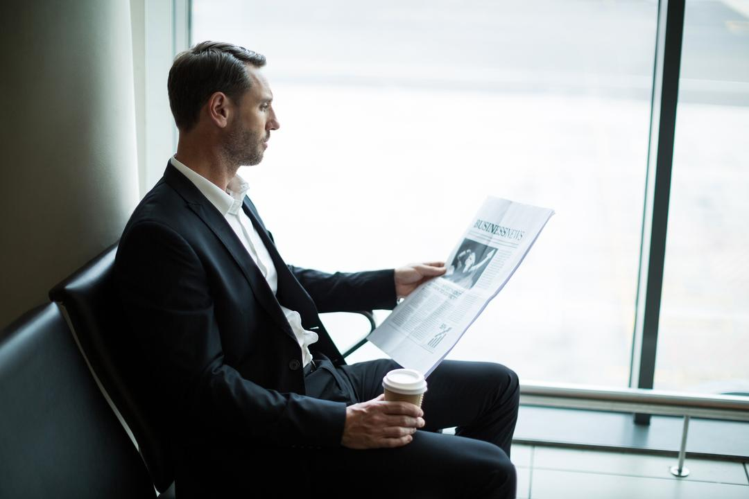 Businessman having coffee while reading newspaper in waiting area at airport