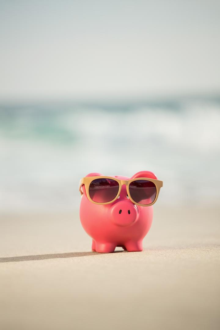 Summer piggy bank with sunglasses on sand at beach Free Stock Images from PikWizard