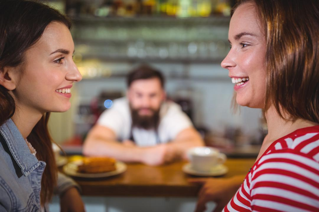 Smiling female friends sitting at counter and interacting in café Free Stock Images from PikWizard