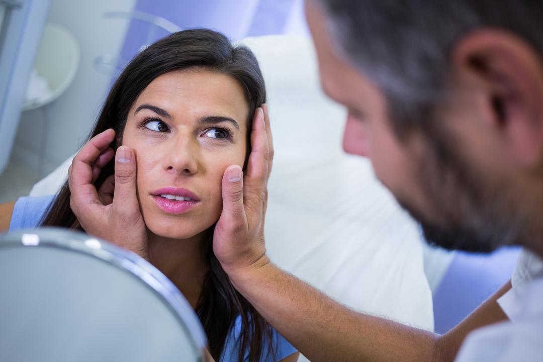 Doctor checking patients skin after cosmetic treatment at clinic