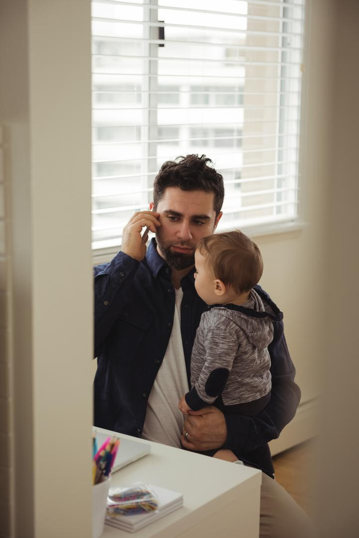 Father talking on mobile phone while holding his baby at home