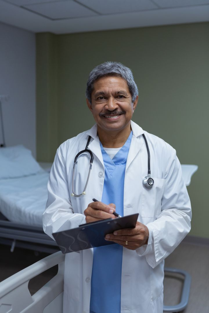 Front view of mature male doctor looking at camera while writing on clipboard in medical ward at hospital Free Stock Images from PikWizard