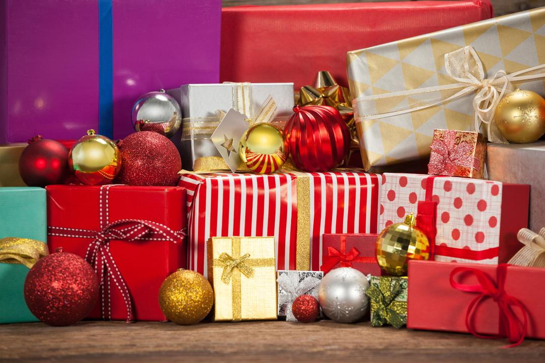 Wrapped gift boxes and baubles on wooden table during christmas time