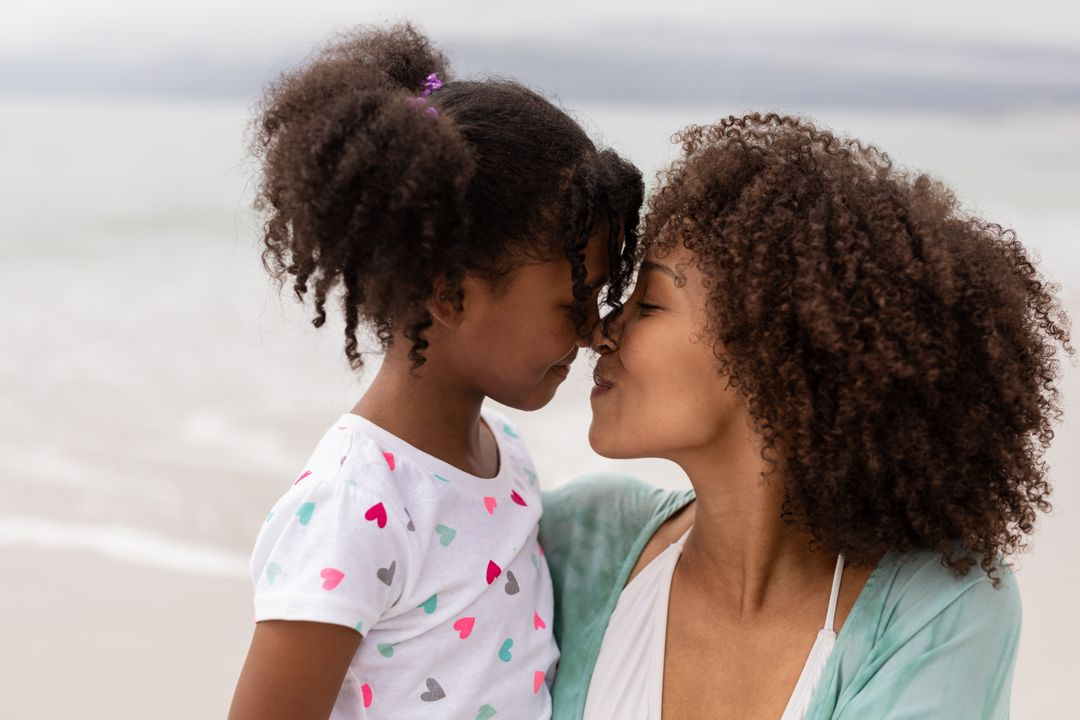 Side view close up of happy young mixed-race mother and daughter rubbing noses at beach on a sunny day.