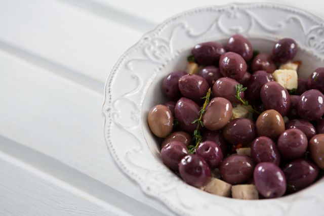 Marinated olives with herbs in a bowl on table