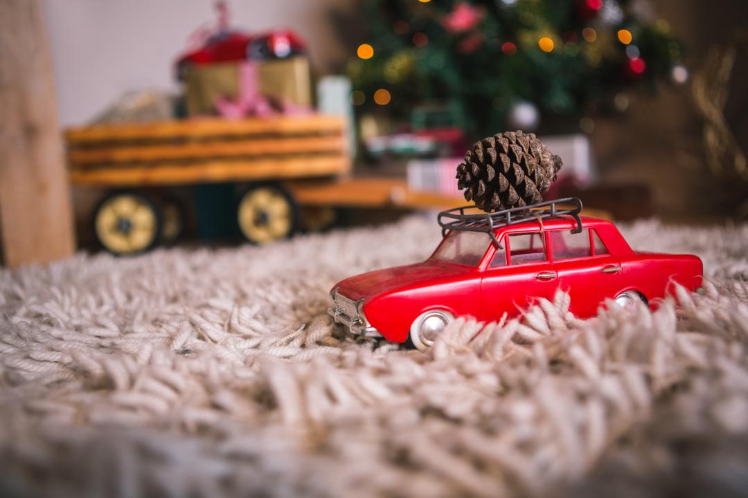 Toy car carrying christmas pine cone on fur carpet