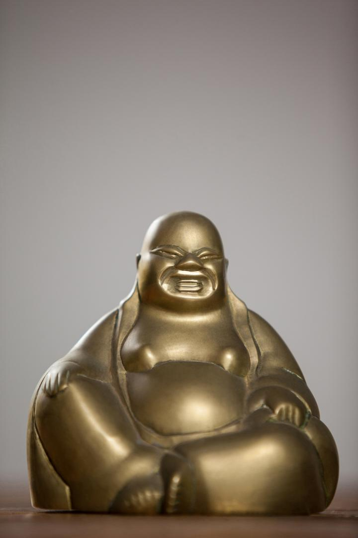 Gold painted laughing buddha figurine on wooden table