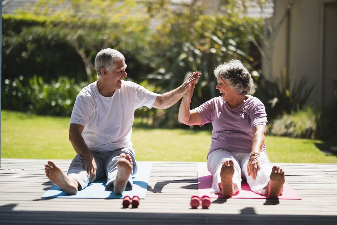Cheerful senior couple giving high five while exercising together on mat at porch Free Stock Images from PikWizard