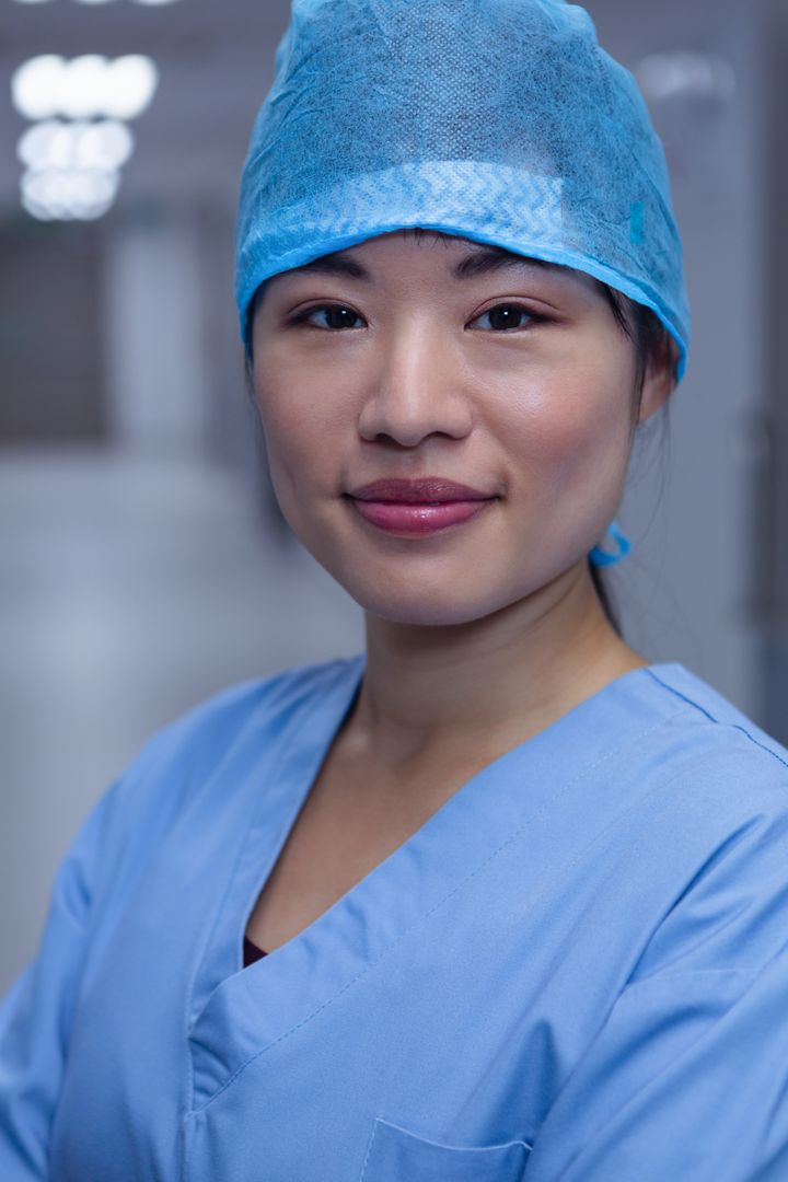 Close-up of female surgeon looking at camera in corridor at hospital