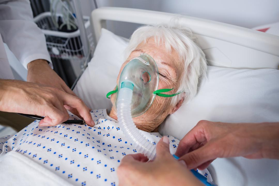Doctors examining senior patient with stethoscope in hospital bed