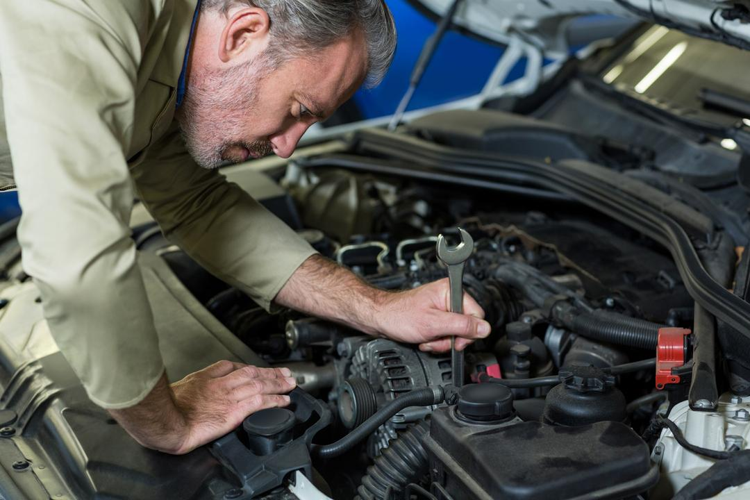 Mechanic servicing a automobile car engine in repair garage