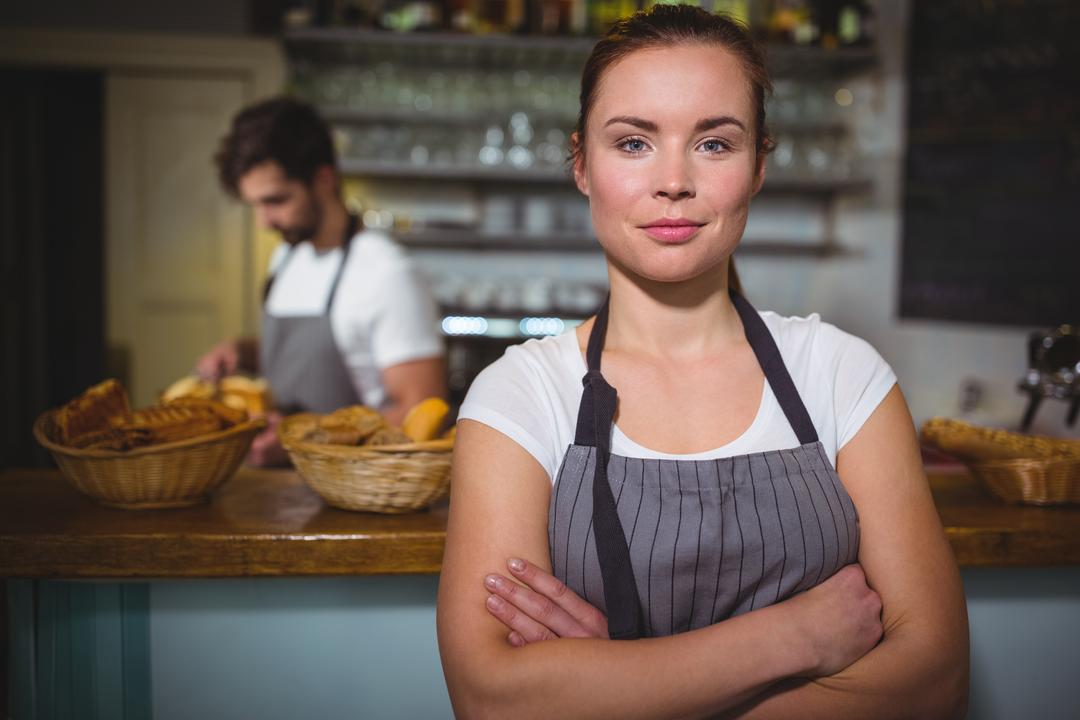 Portrait of waitress standing with arms crossed in café