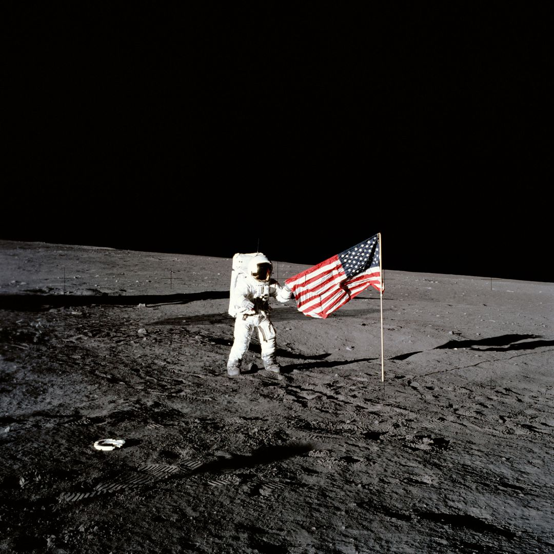 "AS12-47-6897 (19 Nov. 1969) --- Astronaut Charles Conrad Jr., Apollo 12 commander, stands beside the United States flag after it was unfurled on the lunar surface during the first extravehicular activity (EVA), on Nov. 19, 1969. Several footprints made by the crewmembers can be seen in the photograph. While astronauts Conrad and Alan L. Bean, lunar module pilot, descended in the Lunar Module (LM) ""Intrepid"" to explore the Ocean of Storms region of the moon, astronaut Richard F. Gordon Jr., command module pilot, remained with the Command and Service Modules (CSM) ""Yankee Clipper"" in lunar orbit."