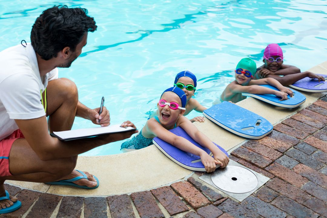 Male instructor writing on clipboard with little swimmers at poolside Free Stock Images from PikWizard