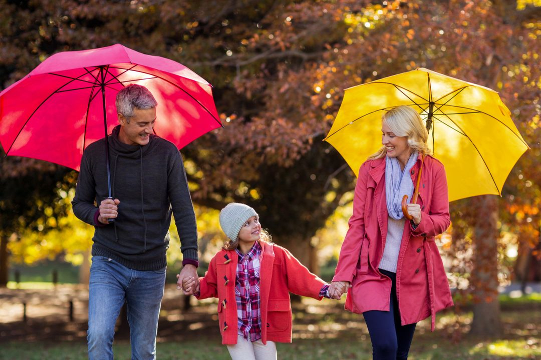 Cheerful parents with daughter walking at park while holding umbrella at park Free Stock Images from PikWizard