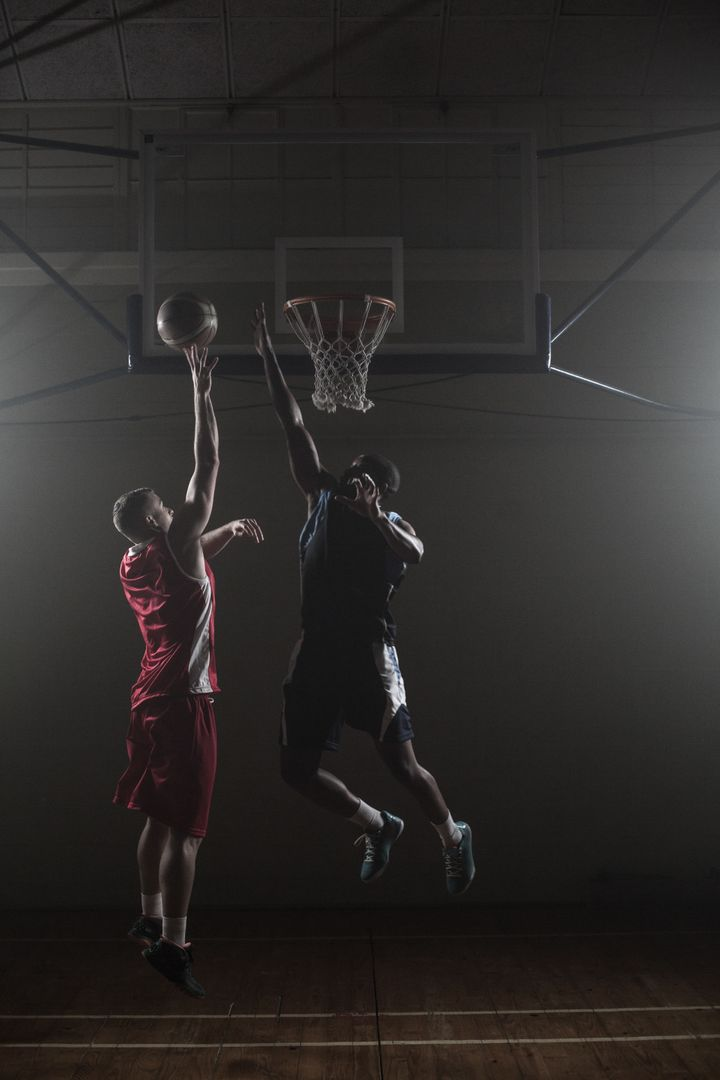 Basketballs player trying to scoring a basket while one trying to block him Free Stock Images from PikWizard