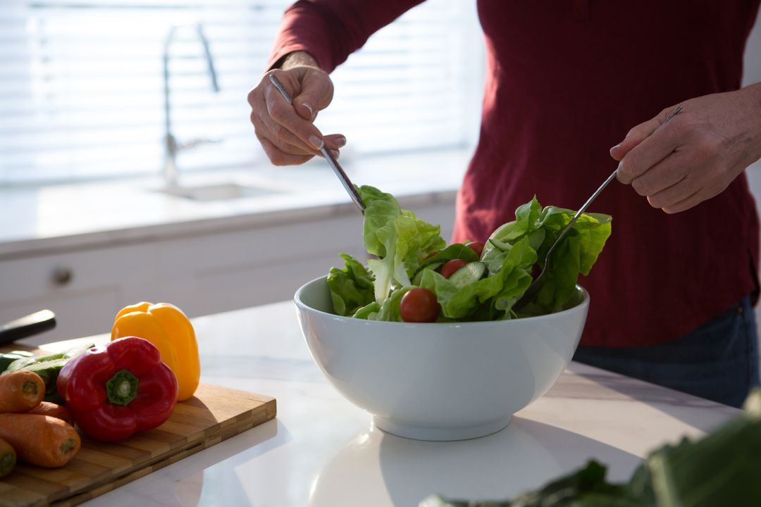 Mid section of woman preparing salad in kitchen Free Stock Images from PikWizard
