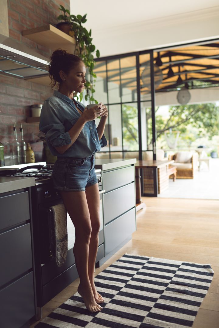 Woman having coffee in kitchen at comfortable home