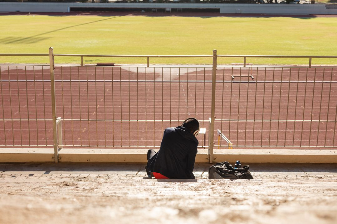 Rear view of fit, mixed race male athlete at an outdoor sports stadium, preparing for workout in the stands wearing headphones. Athletics sport training. Free Stock Images from PikWizard