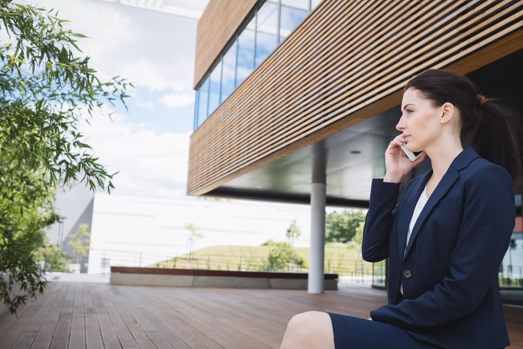 Businesswoman sitting outside office building and talking on mobile phone