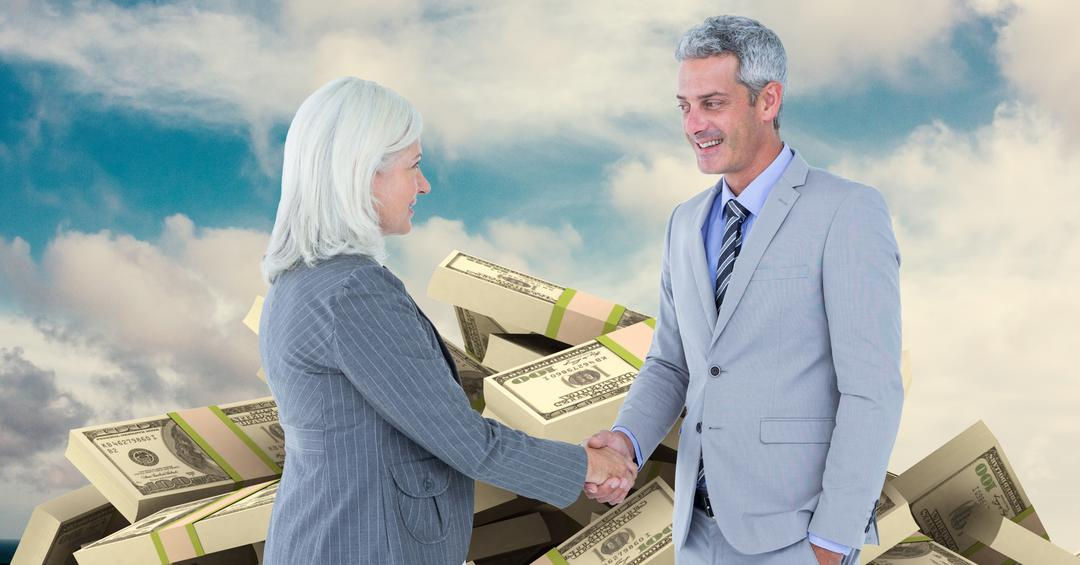 Business people shaking hands with money in background