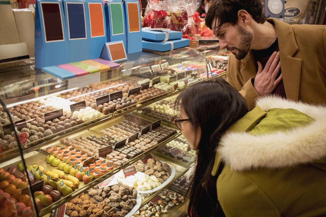Couple looking at desserts at the dessert counter in the supermarket Free Stock Images from PikWizard