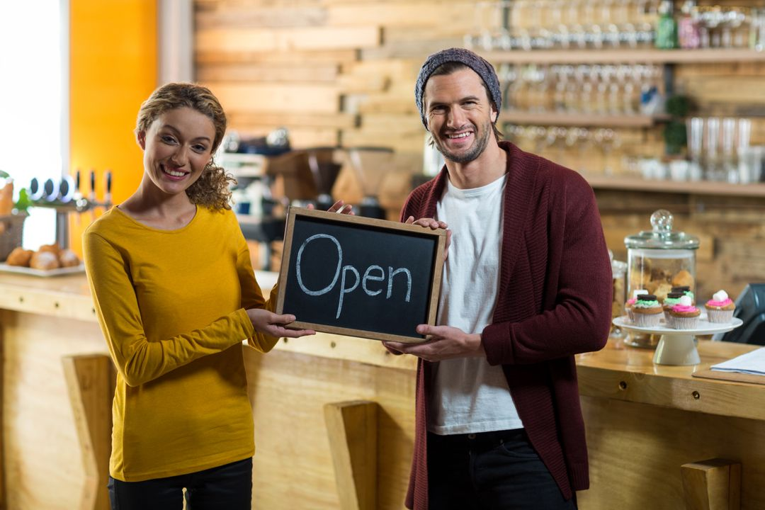 Portrait of smiling owners standing with open sign board in cafe Free Stock Images from PikWizard