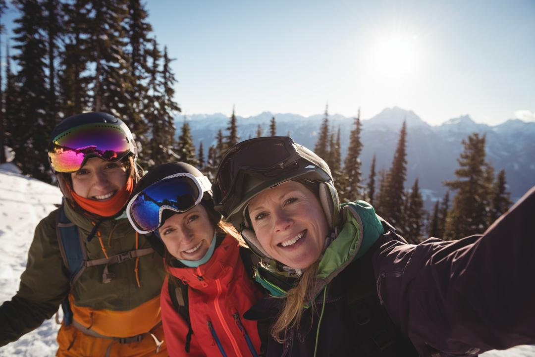Portrait of three female skiers standing together on snow covered mountain