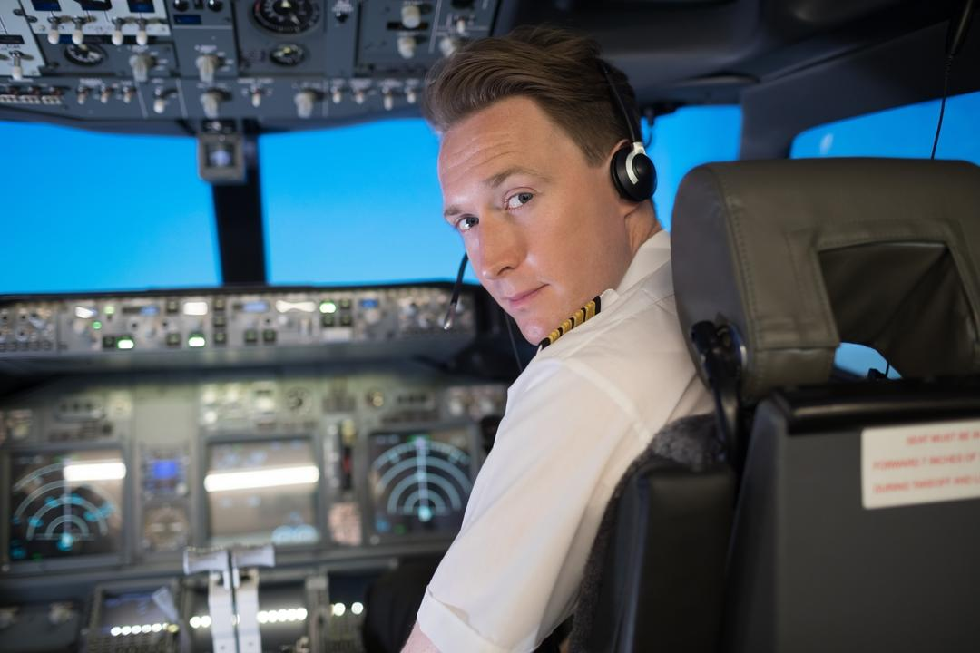 Portrait of handsome young male pilot wearing headphones while sitting on seat in airplane cockpit Free Stock Images from PikWizard