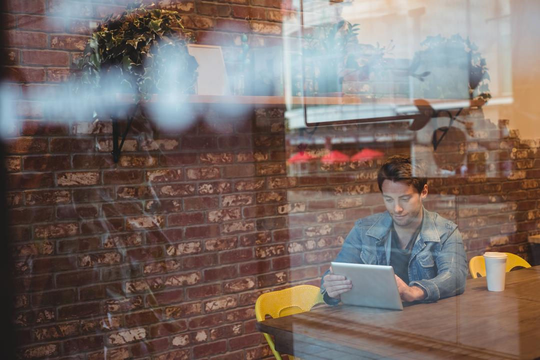 Image of a Man Using an iPad at a Caffee