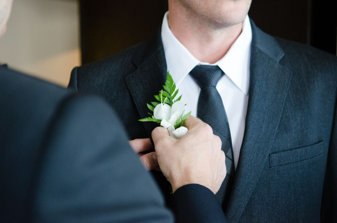 image of a man on his wedding day getting a white flower placed on his suit