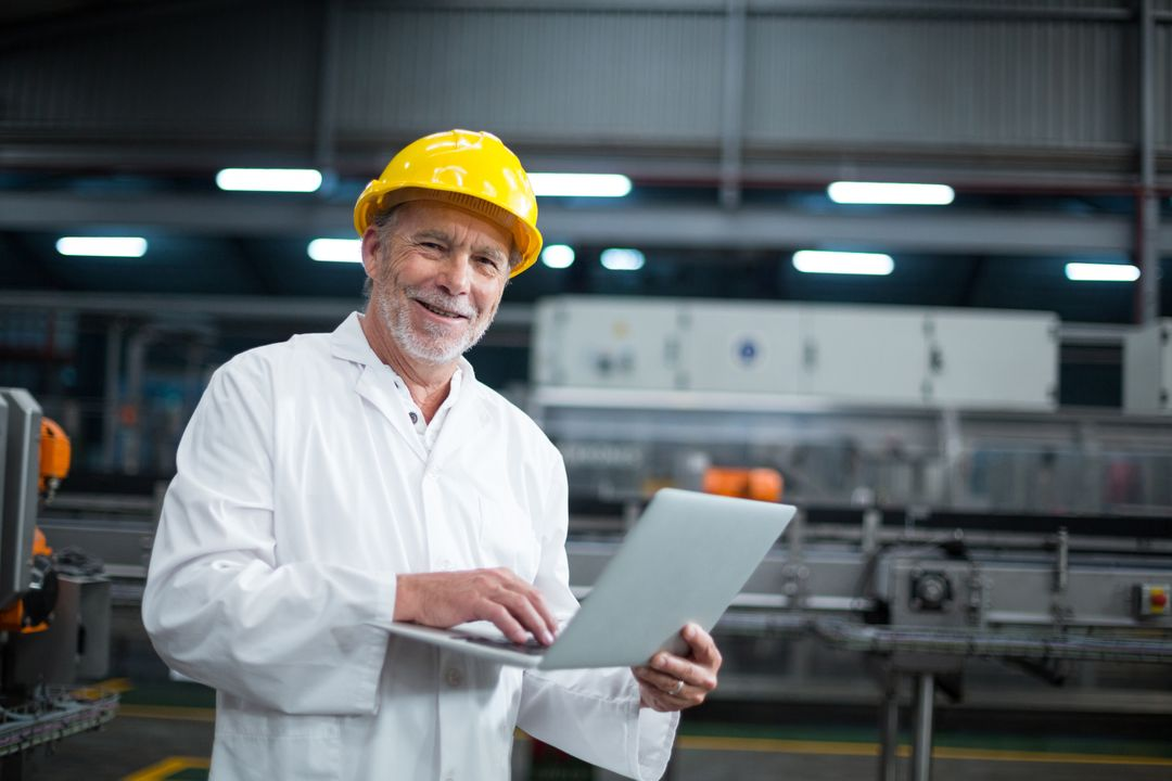 Portrait of factory engineer using laptop in drinks production plant Free Stock Images from PikWizard